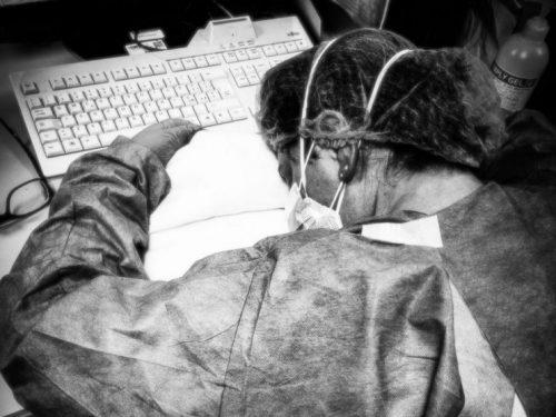 Infermiera sfinita si addormenta con mascherina e guanti